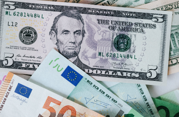 Stack of different currency with photo of men and buildings